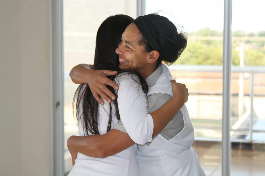 Caregiver hugs patient in Brazil